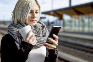 Woman With Coffee Cup Using Mobile Phone At Train Station