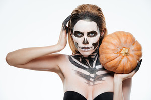 Woman with frightened skeleton makeup holding pumpkin over white background