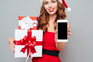 Woman with gifts shows the phone. Santa's helper. Dress and Santa's hat