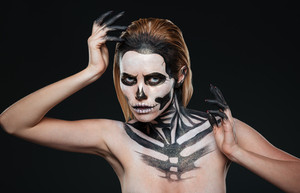 Woman with gothic terrifying makeup posing over black background