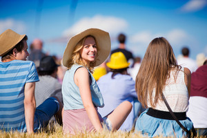 Woman with hat, group of teenagers at summer music festival, sitting on the grass, back view, rear, viewpoint