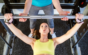 Woman with her personal trainer in a gym working out with weights, bench pressing