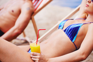 Woman with juice resting in deck chair with man on background