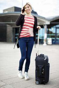 Woman With Luggage Talking On Mobile Phone Outside Railroad Stat