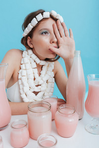 Woman with marshmallow necklace covered half face by hand at the table with pink beverage over blue background