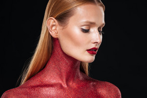 Woman with red bodypainting in profile. Close up portrain. Looking down