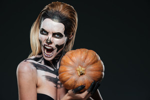 Woman with scared gothic makeup holding pumpkin and shouting over black background