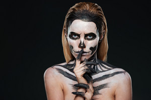 Woman with scared halloween makeup showing silence gesture over black background