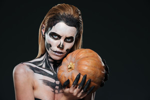 Woman with skeleton halloween makeup holding pumpkin over black background