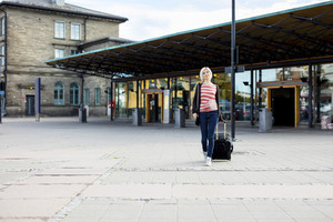 Woman With Wheeled Luggage Walking Outside Train Station