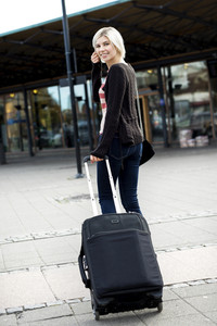 Woman With Wheeled Luggage Walking Towards Train Station