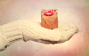Woman with winter gloves holding a small gift box