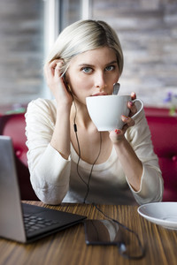 Woman working with laptop computer in cafe