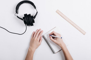 Woman writes a pen in a notebook on a white table, next lie headphones and measuring ruler, top view