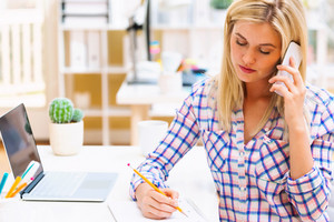 Woman writing in a notebook in a bright office