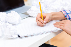 Woman writing on a notebook with crumpled paper balls in an office