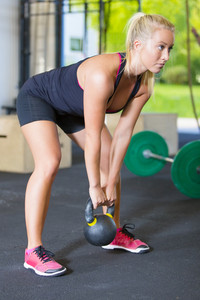Women exercise with kettlebell in fitness gym
