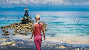 Women Walking Towards an Cute Temple on the Shore by the Sea on Nusa Penida with Dramatic Clouds above Bali, Indonesia