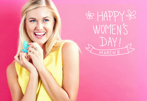 Women's Day text with happy young woman holding a heart cushion on a pink background