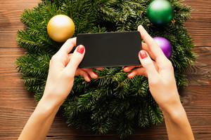 Women's hands with red manicure holding a mobile phone with a touch screen on the background of Christmas decorations