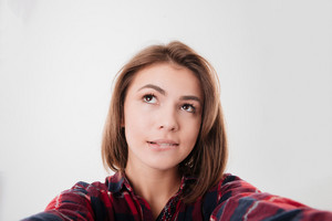 Wondering pretty girl in plaid shirt taking selfie isolated on a white background