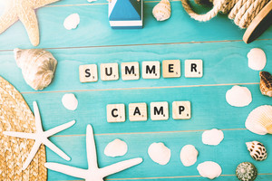 Wood Blocks on Light Blue Table with Assorted Sea Shells and Starfish for Summer Camp Concept