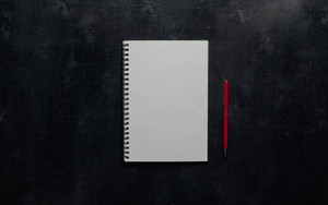 Wooden black office desk table with notebook and red pen . Blank notebook page for input the text in the middle. Top view
