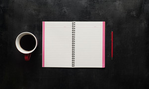 Wooden black office desk table with notebook, pen and  cup of coffee. Blank notebook page for input the text in the middle. Top view
