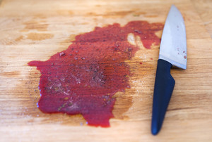 Wooden cutting board with kitchen knife and blood on it