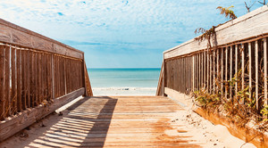 Wooden walkway path leading to the sunny beach