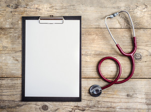 Workplace of a doctor. Stethoscope and clip board on wooden desk background.