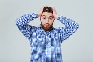 Worried bearded young man standing with hands on head over white background