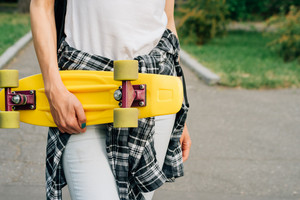Yellow plastic skateboard with green wheels in female hands outdoors in a park