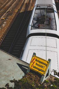 Yellow sign warning for high voltage contact wires above the rails, and white speed train in the background