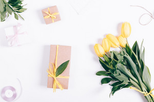 Yellow tulips and gift box lying on white background, top view