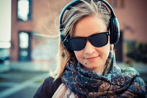 youg beautiful blonde woman listening to music in the city