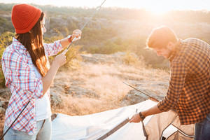 Young active couple setting up a tent