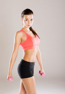 Young active woman with barbell is training in studio