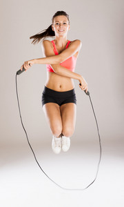 Young active woman with rope is training in studio