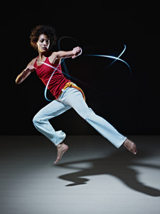 young adult latin american female doing capoeira flying kick in gym, with streaks of led lights all around. Vertical shape, full length, front view, copy space