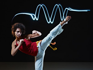 young adult latin american female doing capoeira side kick in gym, with streaks of led lights on top. Vertical shape, full length, front view, copy space