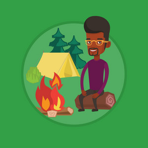 Young african-american man sitting near campfire. Man sitting on a log near campfire. Smiling tourist relaxing near campfire. Vector flat design illustration in the circle isolated on background.