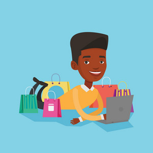 Young african-american man using laptop for shopping online. Smiling customer lying with laptop and shopping bags around him. Man doing online shopping. Vector flat design illustration. Square layout.
