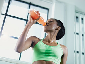 young african american woman in sportswear with energy drink in gym. Horizontal shape, waist up, low angle view