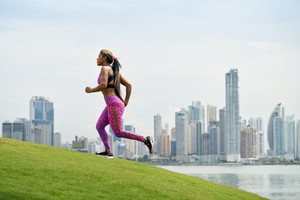Young african american woman running and exercising early morning in the city. She runs on a small hill against the skyline