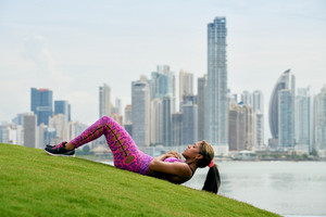 Young african american woman training abdominals and exercising early morning in the city. She trains on grass along the Cinta Costera in Panama City. Long shot