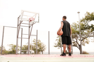 Young african basketball player looking at hoop, shooting at basket outdoor.