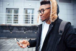 Young african man holding his cellphone in hands and chatting while listen to music. Look at phone.