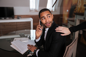 Young African man in suit sitting by the table with phone and meets his friend