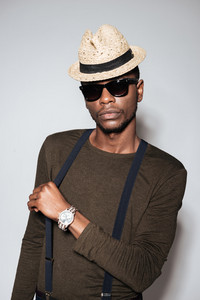 Young african man wearing hat and glasses standing in studio. Isolated over grey background.